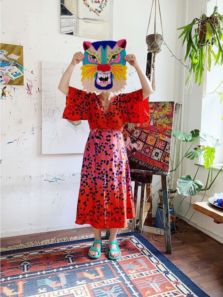 Artist Ina Dyreborg holding her tufted tiger art up to her head